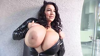 Busty subfuscous in a tight, latex costume, Subrina Lucia is showing us her massive milk jugs