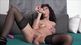 Mature woman shows off working a big toy into her wet holes